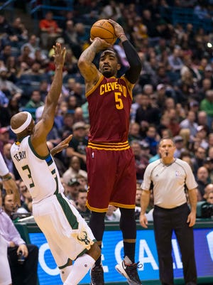 Cavaliers guard J.R. Smith (5) shoots over the outstretched arm of Bucks guard Jason Terry during Tuesday's game.