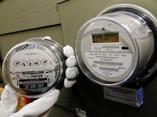 Portland General Electric's old meter with dials is compared to the new digital meter.