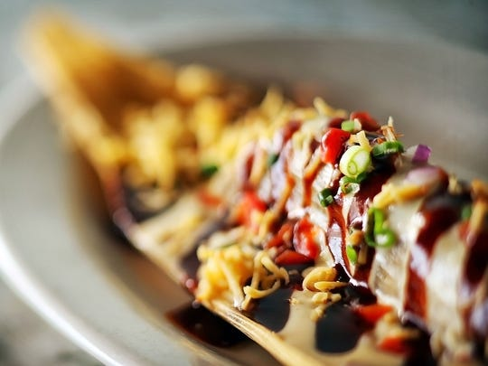 A tasty small plate option, the beef short rib tamale consists of a hand rolled tamale with smoked cheddar cheese sauce, BBQ sauce, and minced peppers at the Belle Tavern on Barboro Alley in downtown Memphis.
