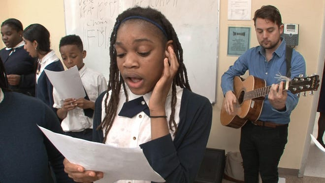 Bourna Moise, 11, sings with other Hope Academy of Asbury Park students Wednesday, March 16, 2016. Lakehouse Academy teacher Colton Kayser, Monmouth Beach, is on the guitar. The program is part of an Asbury Park Music Foundation initiaitve to bring music education into school and will lbe a beneficiary of the AP Music in Film Festival.