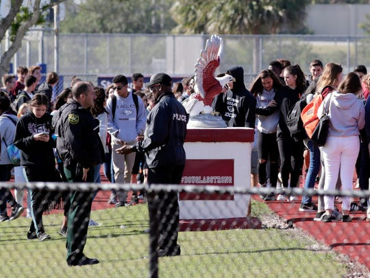 Students at Marjory Stoneman Douglas High School walk out to the school's football field on Wednesday, March 14, 2018, in Parkland, Fla.