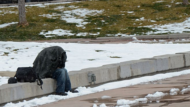 A homeless man covers himself with a jacket as snow begins to fall at Reno City Plaza in downtown Reno on March 2, 2018.