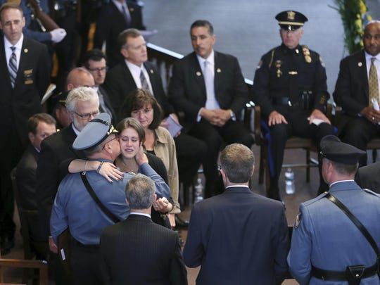 New Jersey State Police Superintendent, Col. Rick Fuentes, left back to camera, consoles Jordan McCarson, wife of fallen New Jersey State Trooper Eli McCarson, Tuesday at Ocean Grove's Great Auditorium as officers and others from around the state gather for the Police Chiefs Foundation's 32nd annual memorial service remembering officers who died in the line of duty.