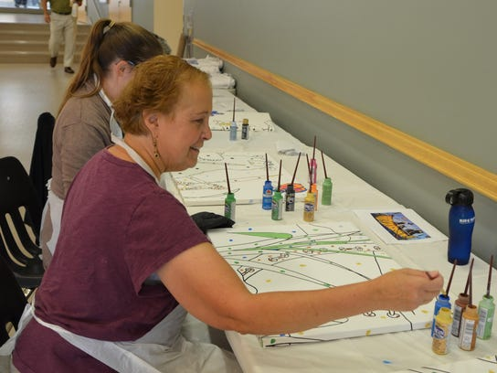 Cancer patient Susan DuCharme works on a picture of
