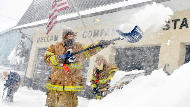 Hellam Fire Company volunteer firefighters Nathan Wolfgang, Cory Beaverson and Josh Sipe shovel out the company's driveway Saturday, Jan. 23, 2016. The firefighters said their week-old snowblower had failed. A snow storm affecting much of the East Coast is expected to bring up to 3 feet of snow to York County, Pa., through Saturday evening.