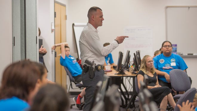 San Juan County Sheriff's Office Detective Eric Barlow speaks with students attending the GenCyber Summer Training Camp Wednesday at San Juan College's Quality Center for Business in Farmington.