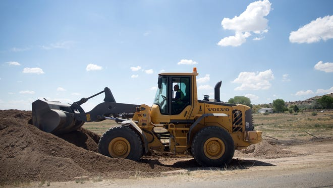 Construction workers prepare the site where a connection between the old Harvest Gold water system and the city of Bloomfield system is planned Wednesday on County Road 4903 in Bloomfield.