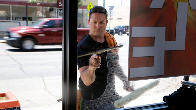 Jeremy Higgins cleans windows at Brown's Shoe Fit Co. in Farmington on Wednesday.