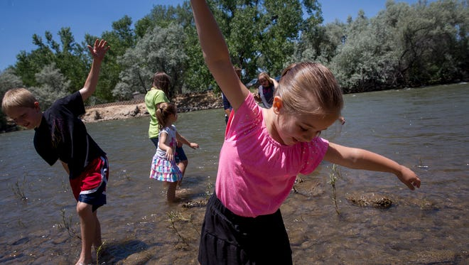 At right, Hyrum Frey and Diana Frey play with the rest of their family June 29 in the Animas River at Berg Park in Farmington.