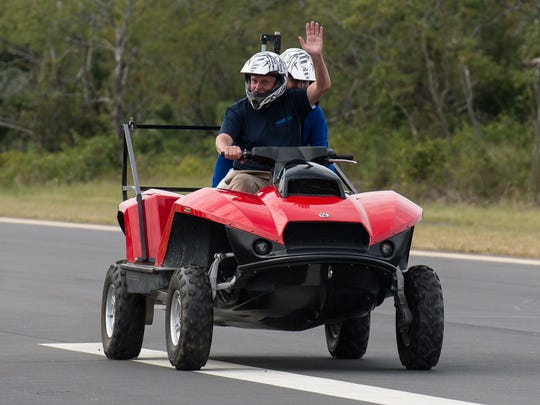 Virginia Governor Terry McAuliffe waves to the crowd while driving a quad ski vehicle with University of Delaware professor Art Trembanis as a passenger at Wallops Flight Facility on Friday, Sept. 22, 2017.