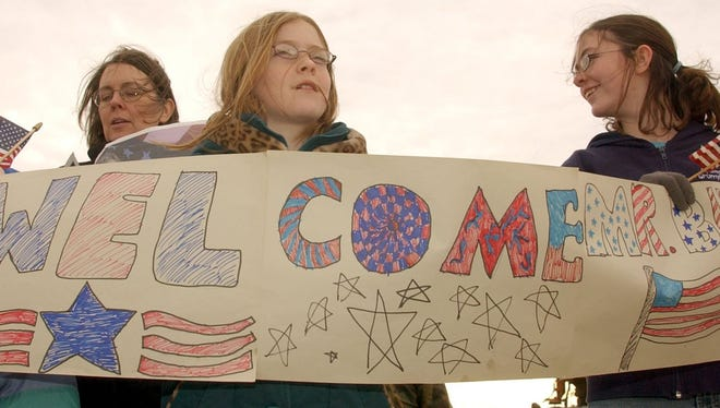 Deirdre Johnson, 11, and her sister, Brenna, 13, hold a welcoming sign as President Bush leaves the airport Thursday, Feb. 3, 2005, in Great Falls.