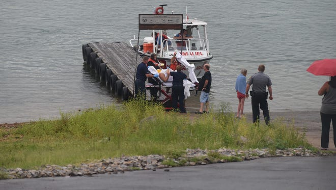 Emergency personnel cover a woman Sunday evening at Robinson Point Park after radio traffic indicated she was injured while jumping from a popular bluff on Norfork Lake.