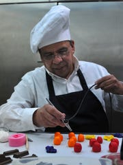 David Molina prepares toppings for a groom''s cake in a small kitchen inside Millwright Marketplace & Flowers in Archer City. Molina opened his cake business in mid-August and will specialize in many different deserts.