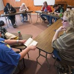 Linda Hansen, left, talks with discussion leader Dannelle Gay, right, during a book club gathering for the homeless.