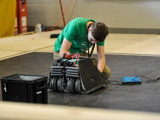 A competitor makes last moment adjustments to his robot during the sumo competition in which the goal is to push the other robot out of the ring.