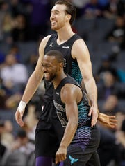 Charlotte Hornets' Frank Kaminsky, back, and Kemba Walker celebrate during a timeout in the first half of the team's NBA basketball game against the Indiana Pacers in Charlotte, N.C., Friday, Feb. 2, 2018.