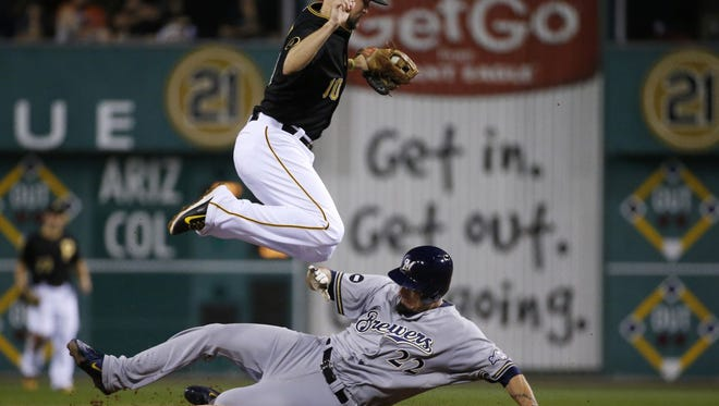 Milwaukee Brewers starting pitcher Matt Garza (22) takes Pittsburgh Pirates shortstop Jordy Mercer out of turning a double play on Brewer's Scooter Gennett during the third inning of a baseball game in Pittsburgh Saturday, Sept. 20, 2014. (AP Photo/Gene J. Puskar)