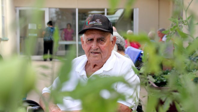 """Enrique """"Kike"""" Viramontes is framed by tomato plants in the patio garden of the Mimbres Memorial Nursing Home in Deming."""