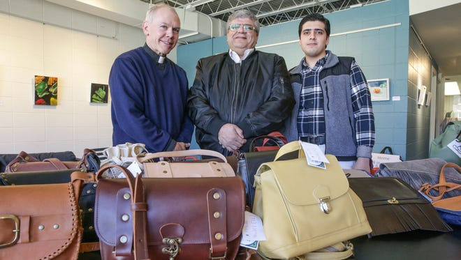Rev. Robert Heimach, a pastor with Irvington Presbyterian Church, left, Purse Maker, Haitham Al Hamwi, center, and his son Mohammed Al Hamwi, right, stand with an assortment of bags hand crafted by Haitham , at the Harrison Center for the Arts, April 7, 2017.  The Alhamwi's are Syrian refugees who have settled in Indianapolis with the help of Rev. Heimach.