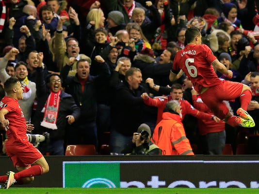 Liverpool's Philippe Coutinho, left, and Liverpool's Dejan Lovren celebrate after scoring the winning goal during the Europa League quarterfinal second leg soccer match between Liverpool  FC and Borussia Dortmund in Liverpool, England, Thursday, April 14, 2016 . (AP Photo/Jon Super)