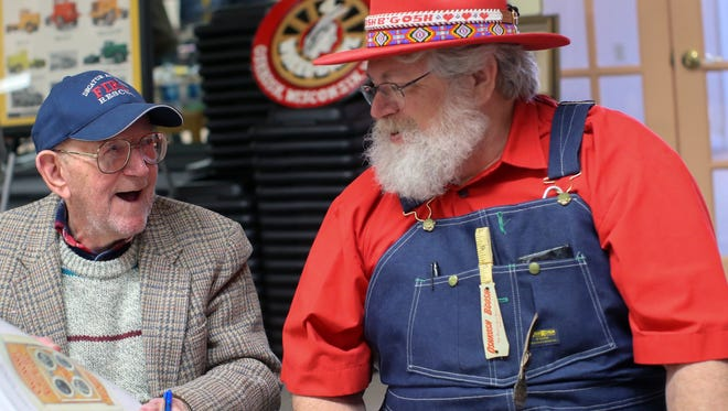 "Clarence ""Inky"" Jungwirth, 95, autographs his book for Tom Beyer, right, wearing Oshkosh B'Gosh clothing during the Oshkosh Memorabilia Club show March 21, 2015, at the Oshkosh Senior Center."
