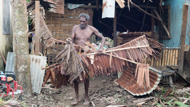 A handout photo provided by UNICEF Pacific on 15 March 2015 shows  a resident clearing debris from his home in Vanuatu on 15 March 2015.