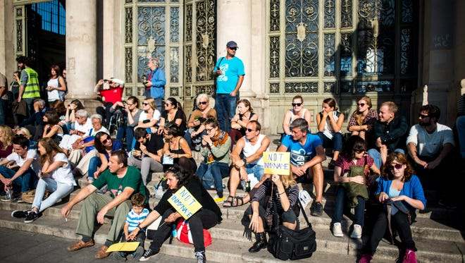 People taking part in a demonstration in support of migrants called 'Solidarity Day' sit on the steps leading to the entrance of the Keleti railway station in Budapest, Hungary, Saturday.