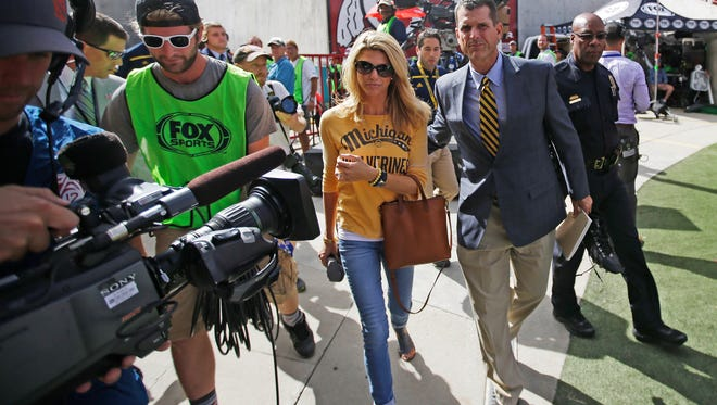 Michigan football coach Jim Harbaugh and his wife, Sarah, arrive for a game against Utah on Sept. 3, 2015, in Salt Lake City.