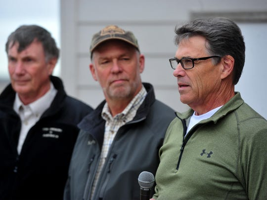 Rick Perry, right, the former governor of Texas, campaigns for gubenatorial candidate Greg Gianforte, center, during a campaign stop at the Sun River Skeet Club north of Great Falls on Wednesday. Tim Macy, left, chairman of Gun Owners of America, looks on as Gianforte and Perry take questioins from the press.