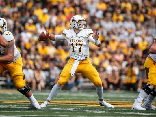 Wyoming quarterback Josh Allen winds back to make a