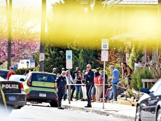 People gather behind yellow police tape at the scene of a fatal shooting in the 200 block of West Maple Street in York on Friday. The son of one resident told his mother he heard several gunshots.