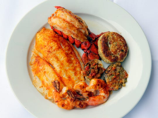 Joe Amiel, owner of Joe Amiel's Bay Pointe Inn, showcases the Fisherman's Broiled Fisherman's Platter with an added Maine lobster tail at the new restaurant in Highlands, NJ Thursday, May 11, 2017.