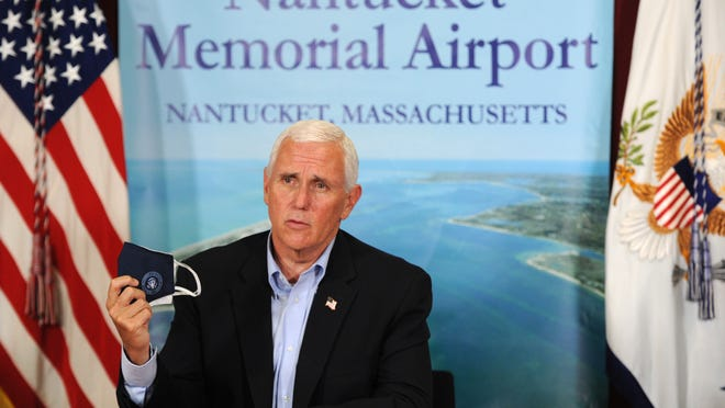 Vice President Michael Pence holds up his face mask advising people to wear them to help prevent the spread of the COVID-19 coronavirus during a visit to Nantucket, Mass., on Saturday afternoon, July 25, 2020, for a campaign fundraising event. Pence and Adm. Brett Giroir met with Massachusetts Gov. Charles Baker at the Nantucket Memorial Airport ARFF Facility Air Rescue and Fire Fighting Facility to discuss COVID-19 response.
