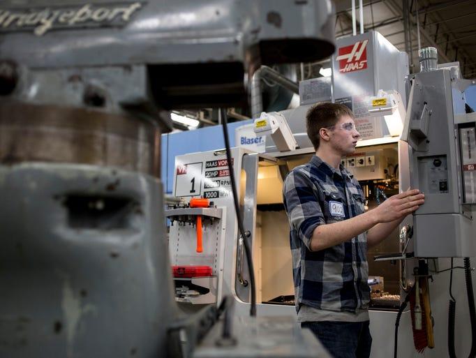Alex Cope, 17, of Clyde Township, programs a CNC machine