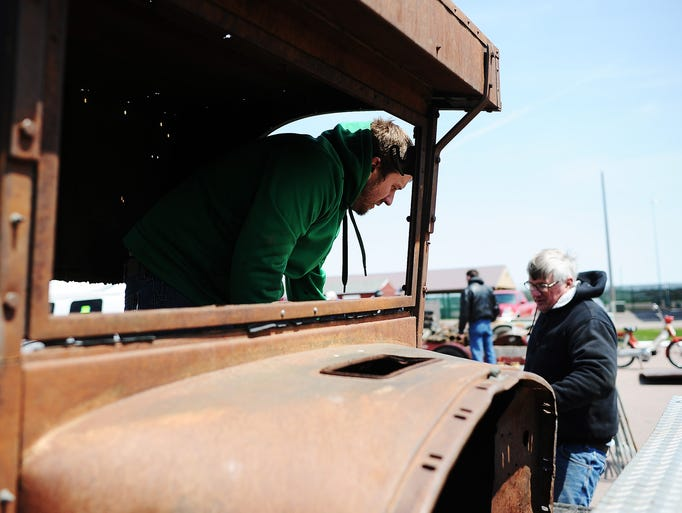 """Dan Bouc, left, and Fred Bouc, of the Sioux City area, load up items they picked up during the Hot Rod Swap Meet, including the cab of an International truck, on Sunday, May 4, 2014, at the W.H. Lyon Fairgrounds in Sioux Falls. Fred said they planned to use the cab for a street rod. """"It's the beginning of a project,"""" Fred said. (Joe Ahlquist / Argus Leader)"""