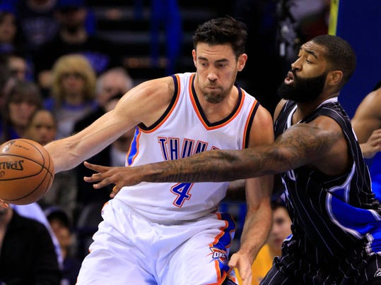 Orlando Magic forward Kyle O'Quinn, right, defends as Oklahoma City Thunder forward Nick Collison, left, drives to the basket during the first quarter of a NBA basketball game in Oklahoma City, Monday, Feb. 2, 2015.  (AP Photo/Alonzo Adams)