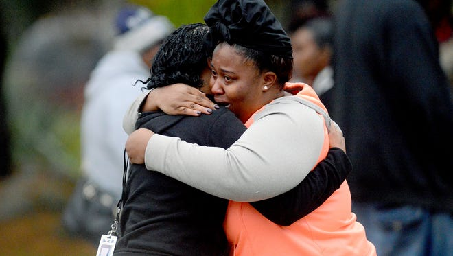Two people embrace as police and family and friends wait at the scene of a murder-suicide Friday, Oct. 28, 2016 in Lansing.