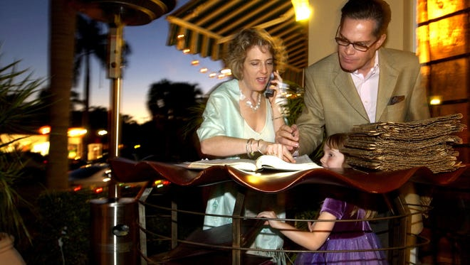 Lisa and Phiippe Boët take reservations outside their restaurant, Chez Boët, in this 2004 file photo in Naples. Their daughter Isabella, then 5, waits for the couple to take a dinner break with her.