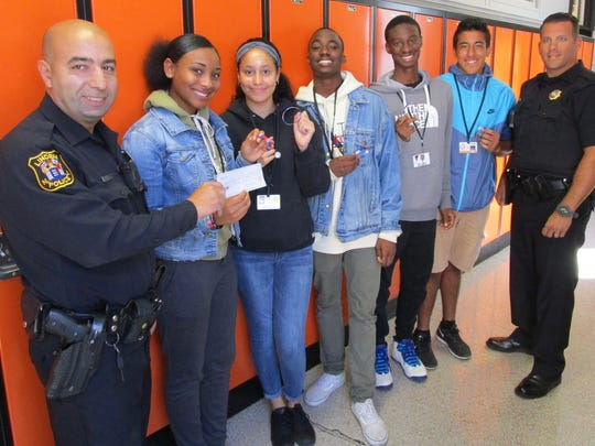 Linden Officer John Halkias, PBA vice president; Peer Pals class members Ariana Moore, Melanie Gomes, Joseph Sobanjo, Lovens Lormilus and Juan Montes; and Sgt. Eric Calleja, sergeant-at-arms for the Linden Superior Officers Association, after the PBA presents a $100 check to the student for their fundraising efforts to assist a Texas high school damaged by Hurricane Harvey.