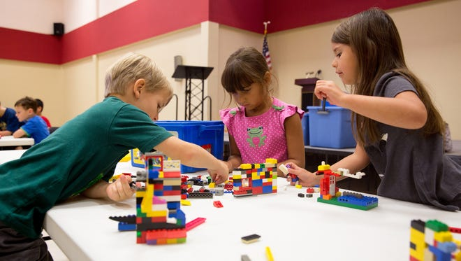 Children play with LEGO bricks.