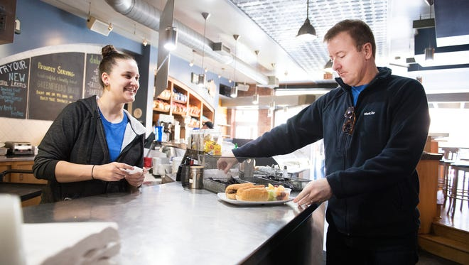 Kayla Campbell serves Joe Wallace his lunch at Soby's on the Side on Friday, March 10, 2017.