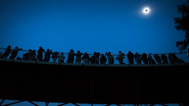 The solar eclipse is in totality over Falls Park Bridge in Greenville on Monday, August 21, 2017.