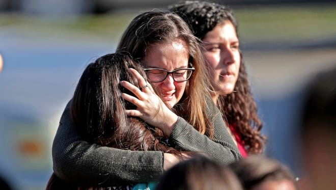 Students released from a lockdown Feb. 14, 2018, embrace following following a mass shooting at Marjory Stoneman Douglas High School in Parkland, Fla.
