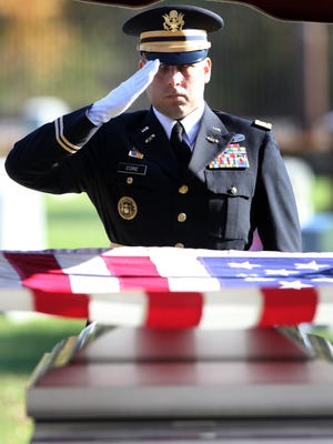 A member of the Indiana National Guard Ceremonial Unit salutes the flag and coffin of Army Spc. Jacob Sexton at Beech Grove Cemetery.
