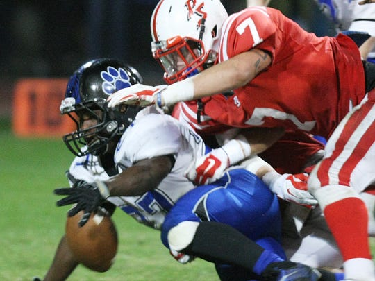 Lions RB Joshua Mosley and Indians LB Riley Hagar chase a loose ball as Cathedral City travels to Palm Springs Friday, November 7, 2014 for a prep football game with playoff implications for both.