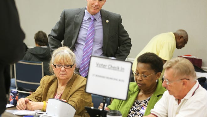 Ohio Secretary of State Jon Husted watches St. Bernard poll workers Gail Webb, Phyllis Austin and Ken Beringhaus use the new electronic voter sign-in system Tuesday morning.
