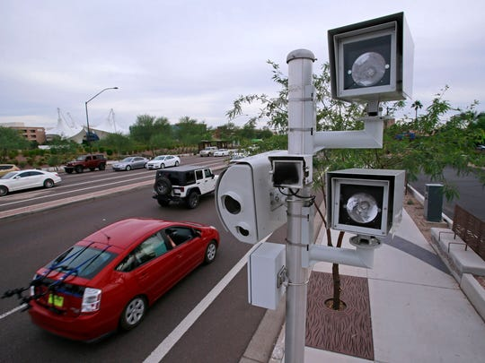 Traffic enforcement cameras stand at the intersection