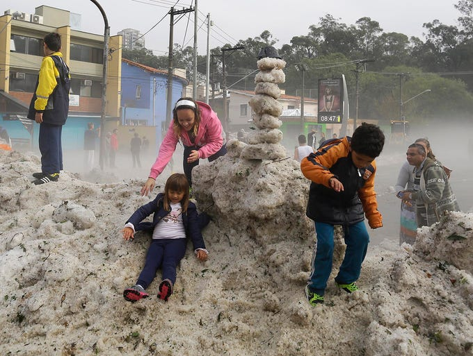 People play on a pile of hail in the Aclimacao neighborhood on May 19 in Sao Paulo, Brazil. An unusual hailstorm blanketed neighborhoods on the south side of the city with up to seven inches of ice.