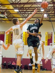Harrisburgs's Naasir Johnson takes a shot at the basket as Shippensburg's Cody Gustafson attempts to block the shot during the Mid Penn boys basketball playoff semifinal in Newville, Pa. on Wednesday, Feb. 10, 2016. Harrisburg defeated Shippensburg 76-35.