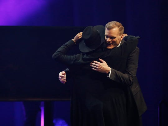 """The Voice"" singer Jon Mero hugs the Rev. Mike Housholder"
